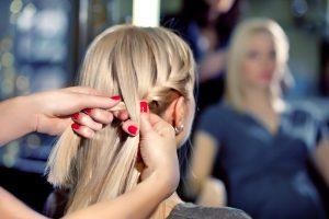 woman getting her hair braided by a hair stylist