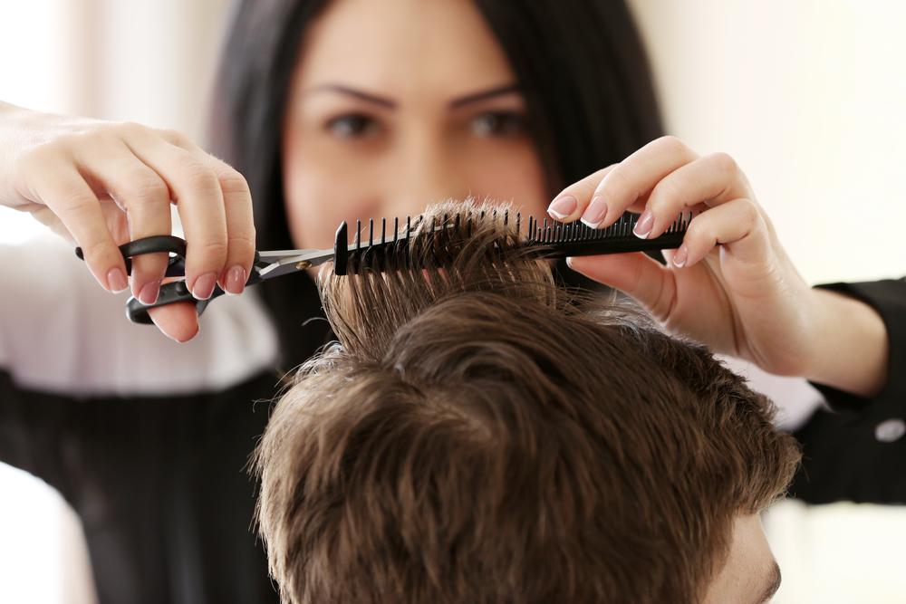 Hair stylist cutting man's hair