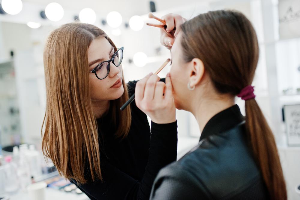 Makeup artist does a brunette client's makeup.