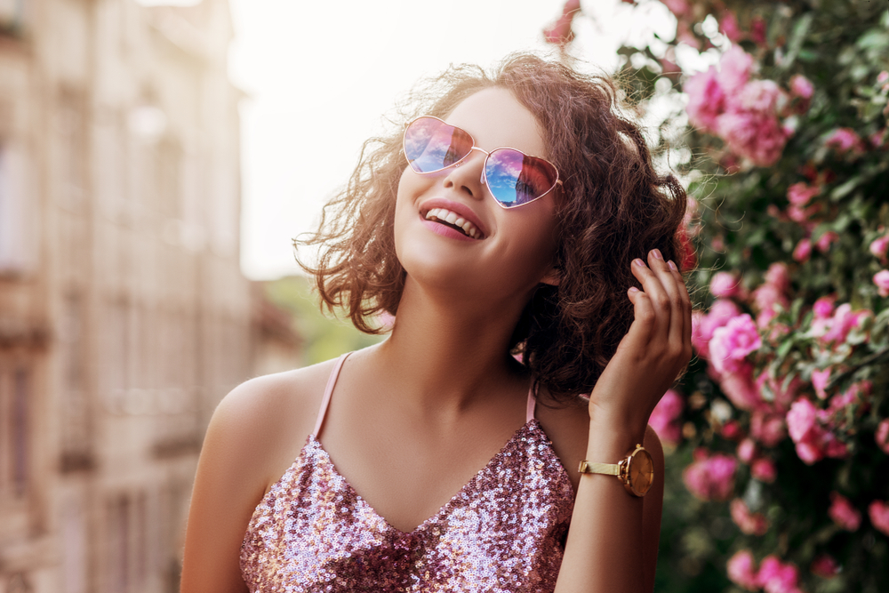 Girl with curly hair wears heart sunglasses and stands by flowers.
