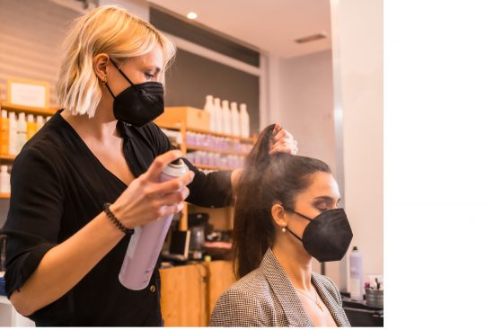 Stylist and client in salon wearing masks